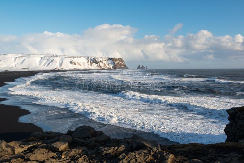 Paisaje del invierno con las pilas de Reynisdrangar, la playa negra y las olas oceánicas, Islandia de la arena imagen de archivo
