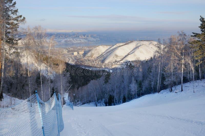 Paisaje del invierno con una cuesta del esquí y una vista de la ciudad de Krasnoyarsk en el horizonte fotografía de archivo libre de regalías