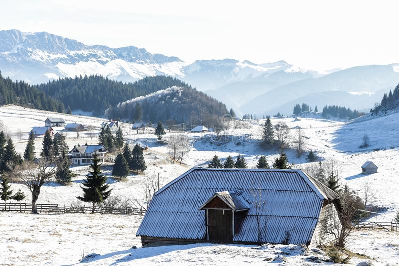 Paisaje del invierno con y casa vieja en el top de la montaña imagen de archivo