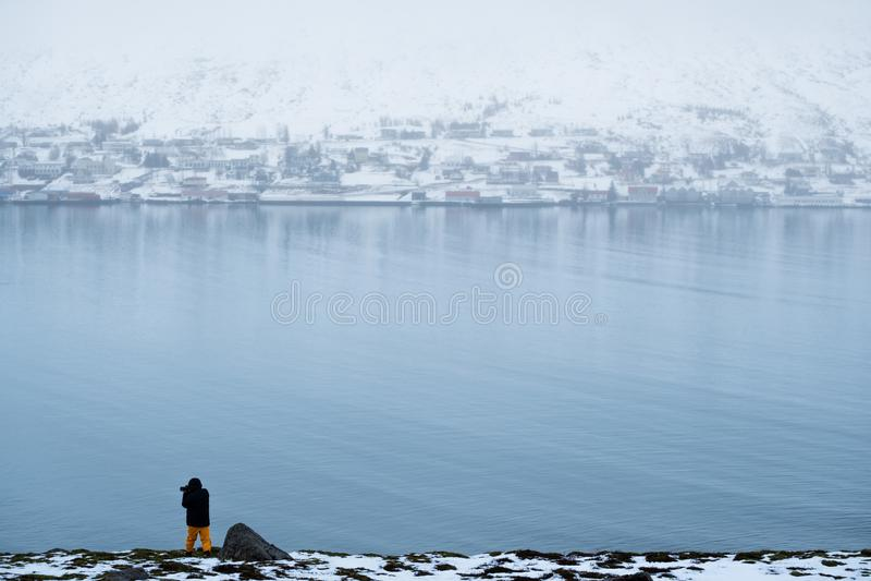 Paisaje del invierno de la ciudad de Akureyri en Islandia con un hombre que toma la fotografía imagen de archivo libre de regalías