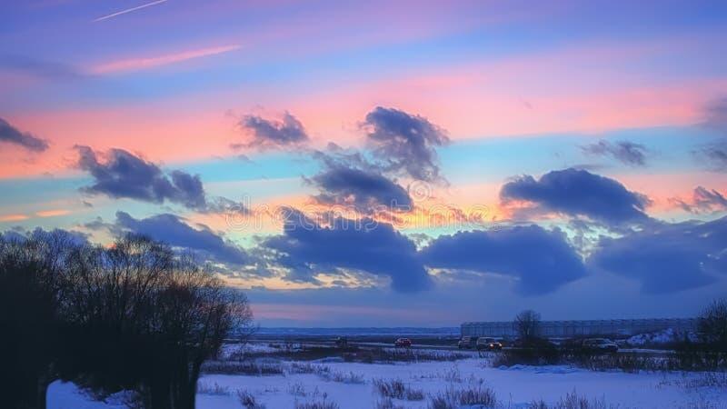 Paisaje del invierno de la noche con las nubes rosadas en la puesta del sol imágenes de archivo libres de regalías