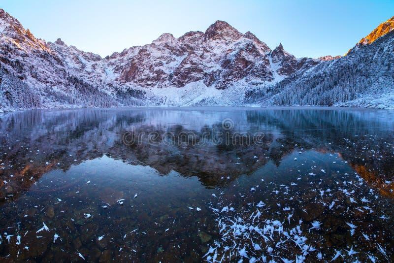 Paisaje del invierno Las montañas reflejaron en el lago congelado foto de archivo