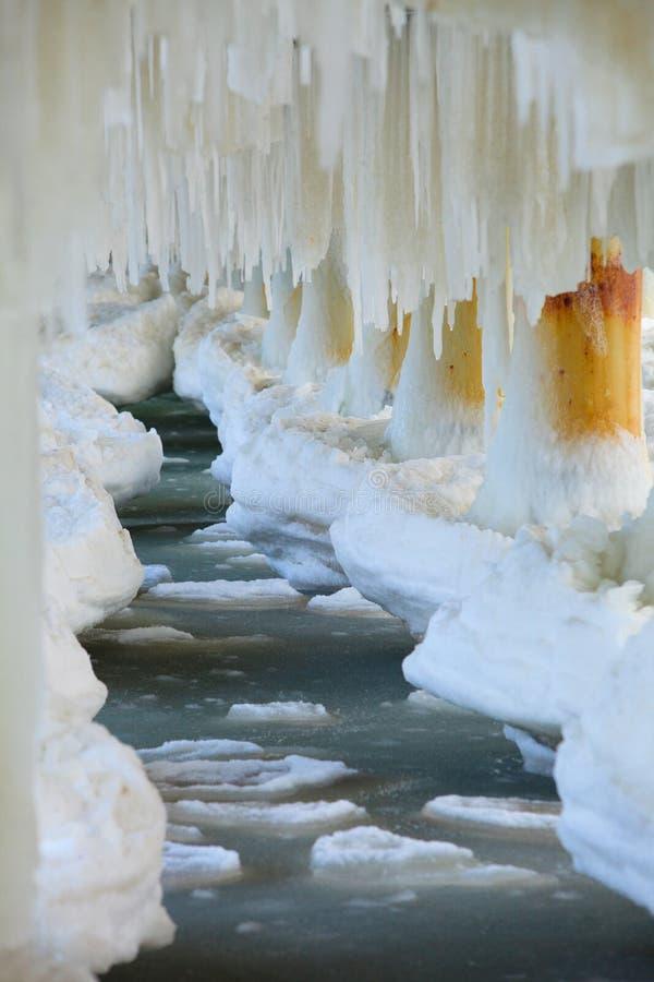 Paisaje del invierno. Mar Báltico. Ciérrese encima de los carámbanos de las formaciones de hielo en polos del embarcadero fotos de archivo