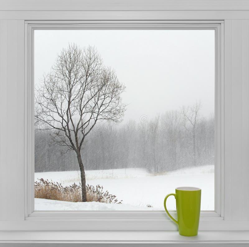 Paisaje del invierno visto a través de la ventana y de la taza verde foto de archivo libre de regalías