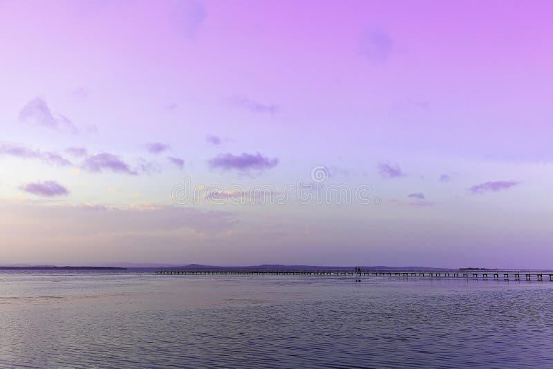 Paisaje del lago con el embarcadero por el cielo violeta en la puesta del sol fotos de archivo libres de regalías
