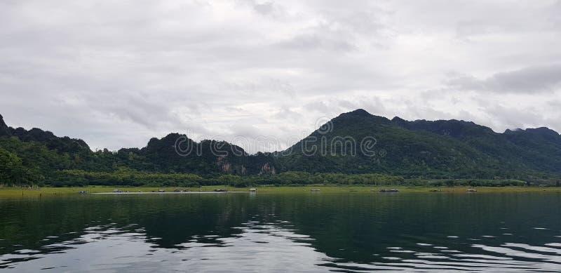 Paisaje del Mountain View con el río o lago, cielo blanco y reflexión en el agua en la presa de Srinakarin foto de archivo