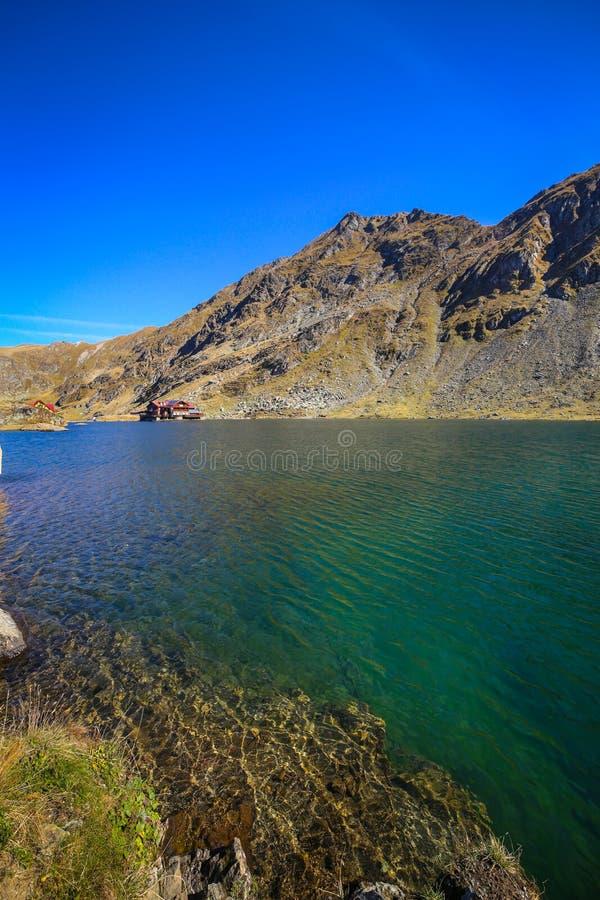 Paisaje del paisaje del otoño con agua que refleja los rayos y la cabina del sol en el lago Balea imagen de archivo