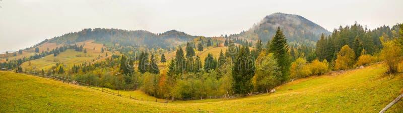 Paisaje del paisaje del otoño con el bosque colorido, las cercas de madera y los graneros del heno en Bucovina, Rumania imagen de archivo