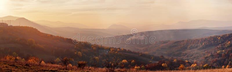 Paisaje del panorama de la puesta del sol del otoño de la montaña con el bosque colorido imagenes de archivo