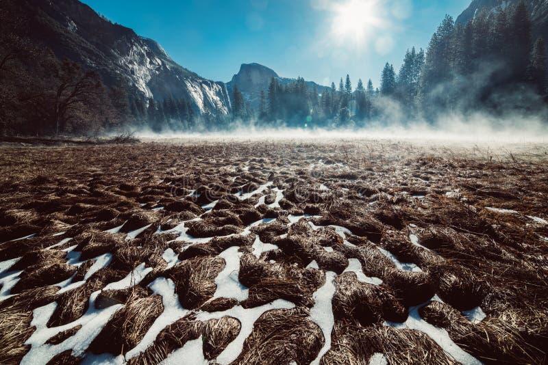 Paisaje del parque nacional de Yosemite por la mañana Campo de hierba debajo de la nieve y niebla con Mountain View imagen de archivo libre de regalías
