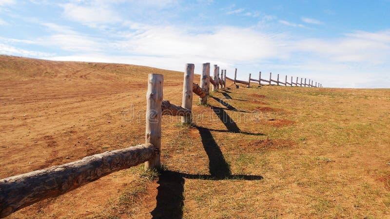 Paisaje del pasto para el ganado, cerca de madera en la pradera, cielo azul con las nubes fotos de archivo libres de regalías