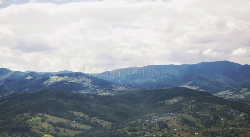 Paisaje del pueblo del valle de la monta?a nublado imagen de archivo