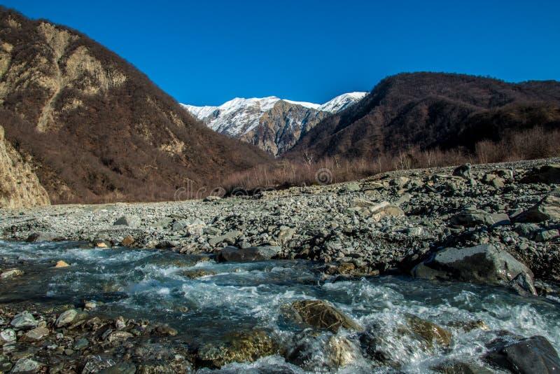 Paisaje del río y de la montaña de la corriente Pico nevado en distancia imagen de archivo libre de regalías