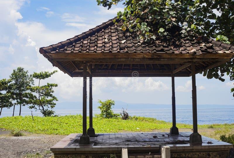 Paisaje del verano con la pérgola de madera vieja por el océano azul foto de archivo