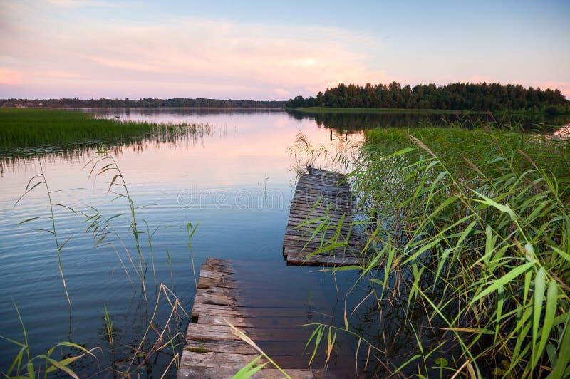 Paisaje del verano con la pasarela vieja en el lago foto de archivo