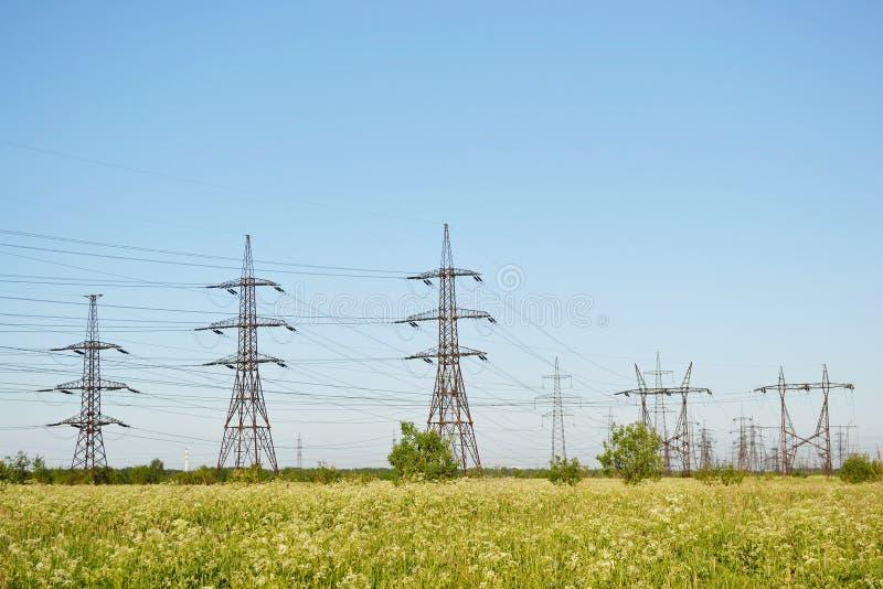 Paisaje del verano con los pilones de la electricidad fotos de archivo