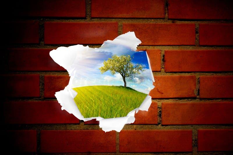 Paisaje del verano detrás del agujero rojo de la pared de ladrillo imágenes de archivo libres de regalías