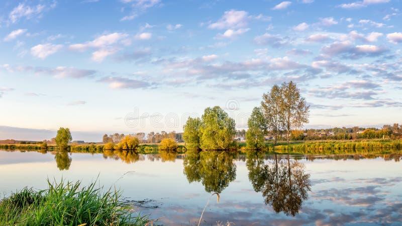 Paisaje del verano en el río con la reflexión de árboles en el agua, Rusia, los Urales, imagen de archivo libre de regalías