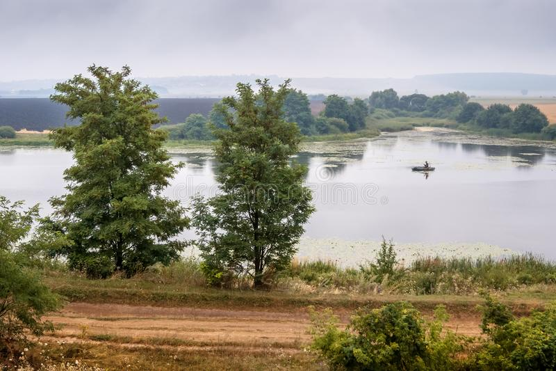 Paisaje del verano: un río con un barco, un cielo cubierto con las nubes fotos de archivo