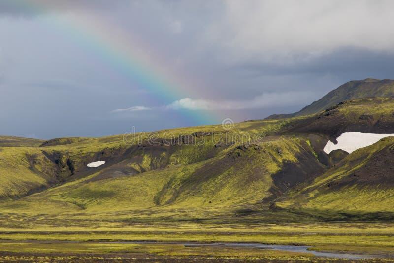 Paisaje dramático de Islandia con una colina verde, una lava negra y parecer del arco iris una luna fotos de archivo