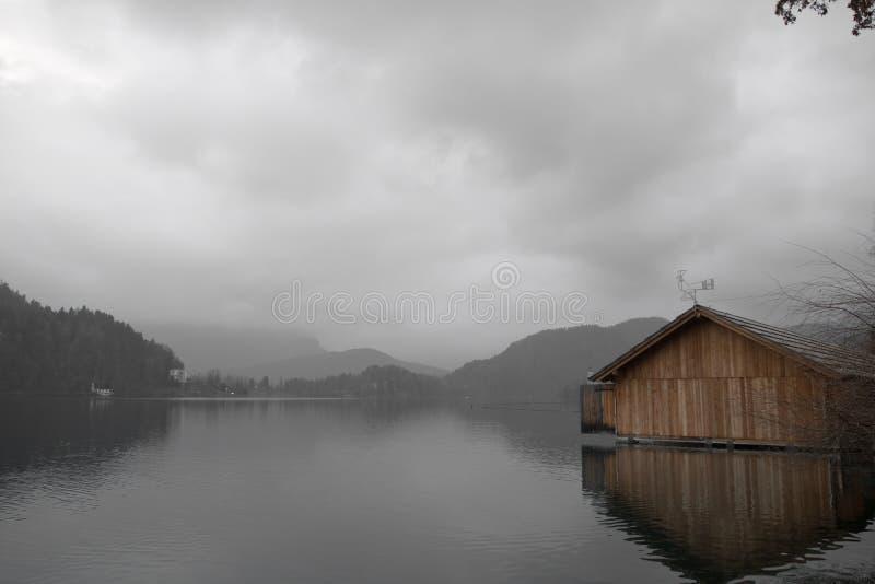 Paisaje dramático del invierno con el varadero de madera en el lago foto de archivo libre de regalías
