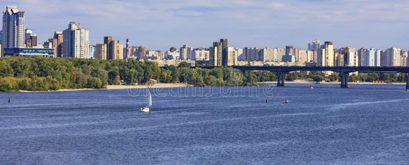 Paisaje: el río Dnipro, zonas residenciales de Kiev a orillas del río y el viejo puente que cruza el río bajo la luz del sol. imagen de archivo