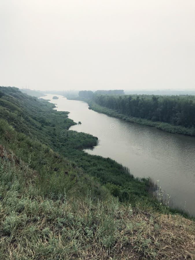 Paisaje en el río de la niebla en un día nublado contra el bosque cubierto en niebla imagenes de archivo