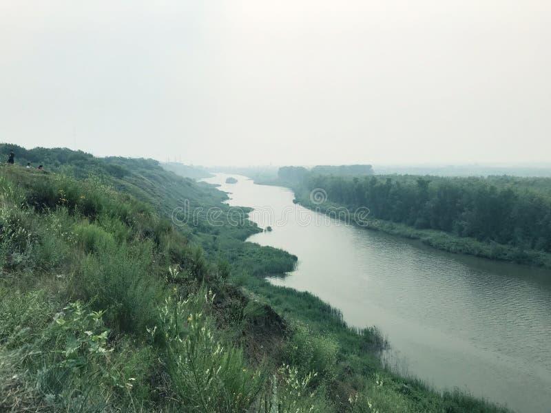 Paisaje en el río de la niebla en un día nublado contra el bosque cubierto en niebla fotos de archivo