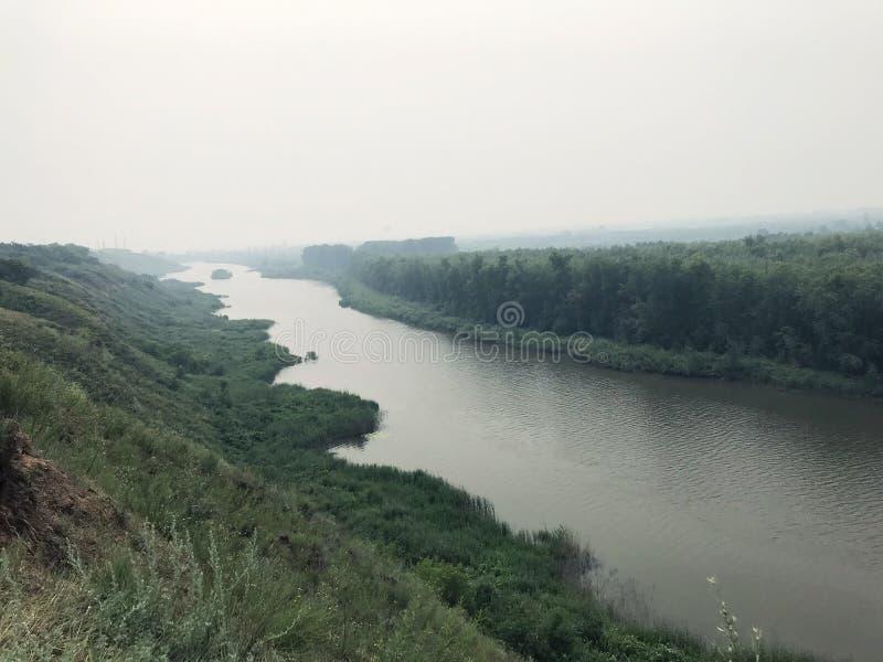 Paisaje en el río de la niebla en un día nublado contra el bosque cubierto en niebla foto de archivo
