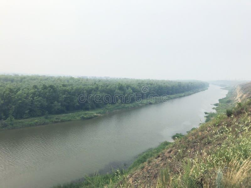 Paisaje en el río de la niebla en un día nublado contra el bosque cubierto en niebla fotos de archivo libres de regalías