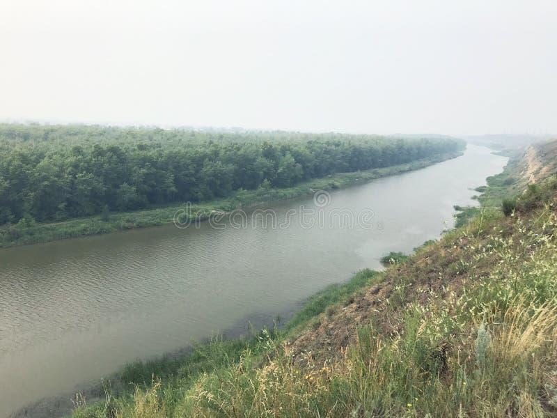 Paisaje en el río de la niebla en un día nublado contra el bosque cubierto en niebla imágenes de archivo libres de regalías