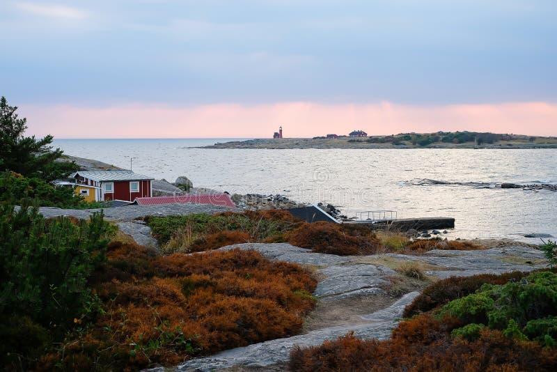 Paisaje escandinavo hermoso con las piedras y el musgo Casas suecas rojas tradicionales Mar en la puesta del sol, el faro encendi imagen de archivo libre de regalías