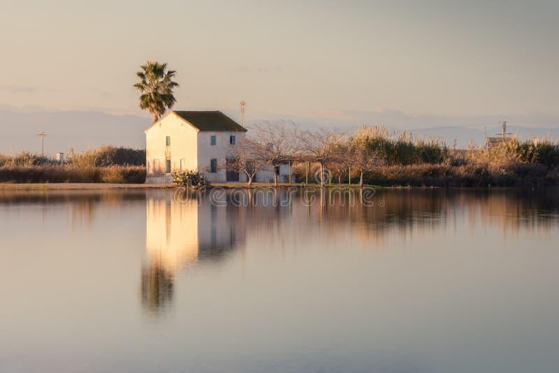 Paisaje hermoso con el cortijo en la laguna de Albufera, la reflexión, el cielo azul y la luz del sol amarilla en salida del sol  fotografía de archivo