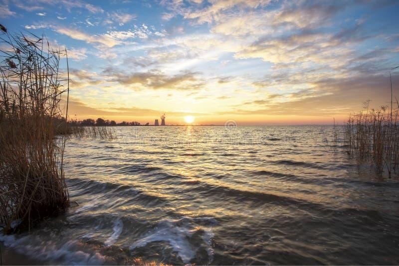 Paisaje hermoso con el lago, cañas, cielo de la puesta del sol foto de archivo