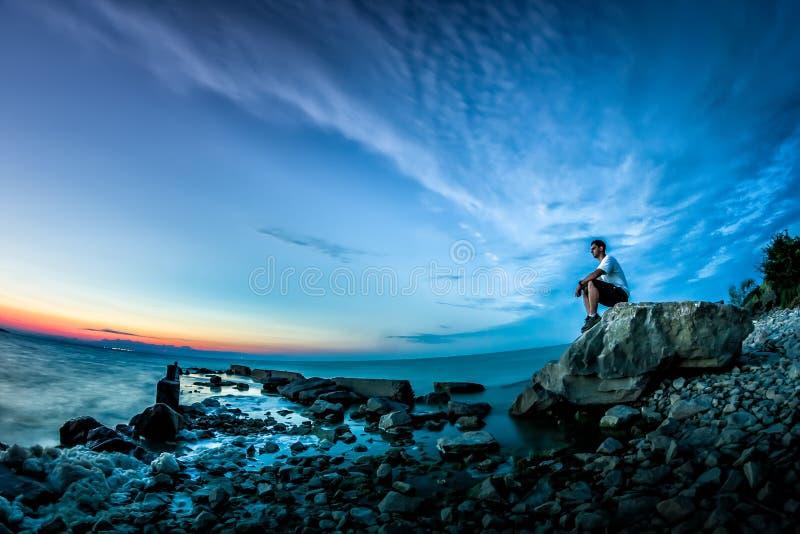 Paisaje hermoso con puesta del sol sobre el lago y un hombre joven que se sienta en una roca imagen de archivo