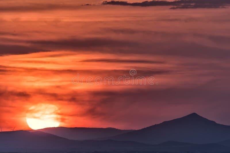 Paisaje hermoso con un sol poniente grande sobre las colinas fotografía de archivo
