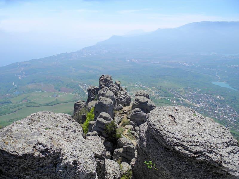 Paisaje hermoso de la montaña con las rocas redondeadas Vista superior del valle habitado con el lago Mesetas distantes de la mon imagen de archivo libre de regalías