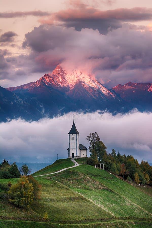 Paisaje hermoso de la salida del sol de la iglesia Jamnik en Eslovenia con el cielo nublado foto de archivo