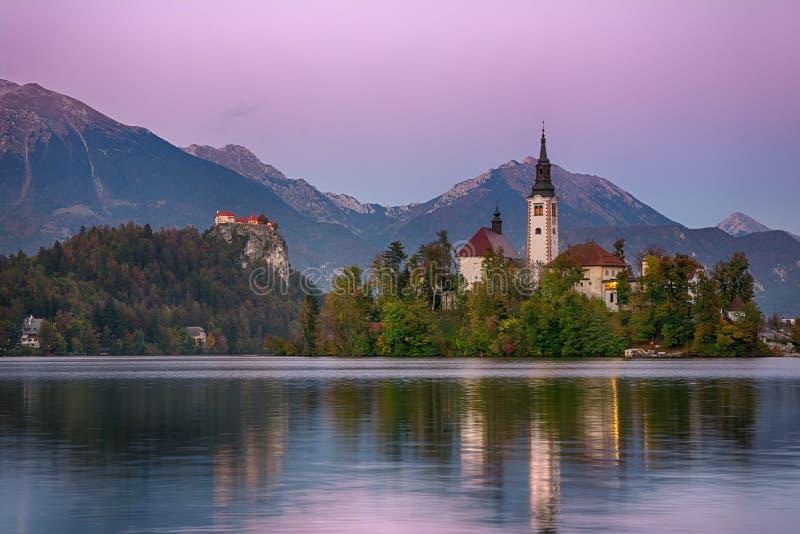Paisaje hermoso de la salida del sol del lago famoso sangrado en Eslovenia con la pequeña iglesia en la isla verde en el cielo nu imagenes de archivo