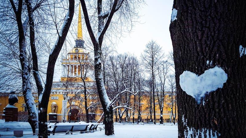 Paisaje hermoso del invierno con el corazón de la nieve en tronco de árbol y el chapitel del edificio del Ministerio de marina, S imagenes de archivo