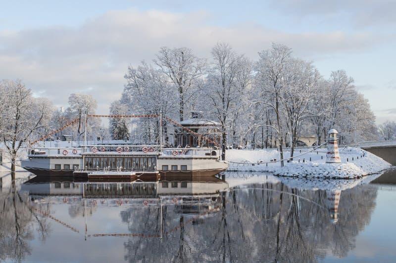 Paisaje hermoso del invierno con la cafetería en la forma del barco con la reflexión agradable en agua foto de archivo libre de regalías