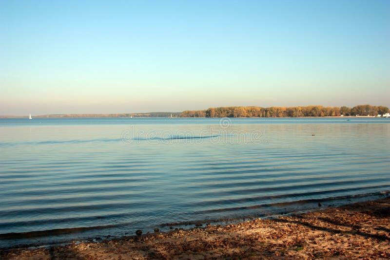 Paisaje hermoso del lago, y puesta del sol Ondas y línea azules del horizonte en el agua Fondo hermoso fotos de archivo libres de regalías