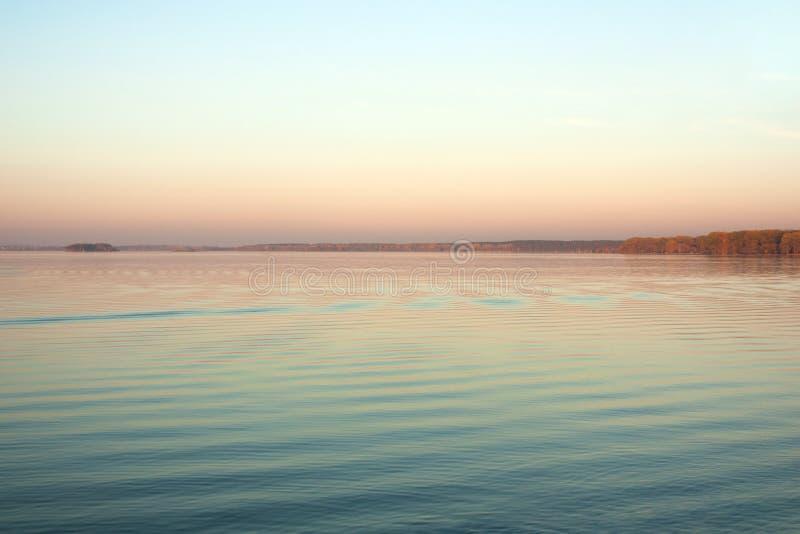 Paisaje hermoso del lago, y puesta del sol Ondas y línea azules del horizonte en el agua Fondo hermoso fotos de archivo