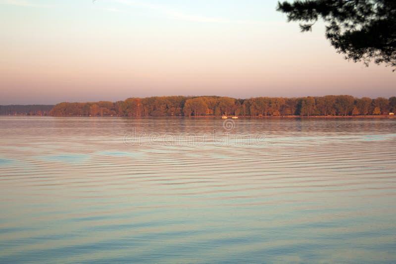 Paisaje hermoso del lago, y puesta del sol Ondas y línea azules del horizonte en el agua Fondo hermoso imagen de archivo libre de regalías