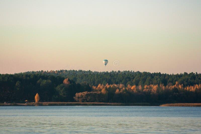 Paisaje hermoso, globo y puesta del sol del lago Línea azul de las ondas, del barco y del horizonte en el agua Fondo hermoso foto de archivo