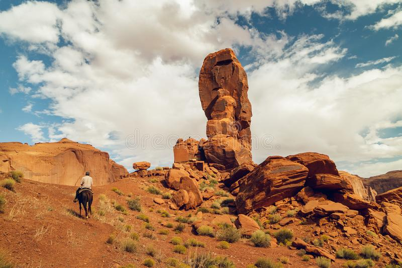 Paisaje hermoso, valle del monumento Silueta del jinete en un caballo, rocas y un cielo nublado imagen de archivo