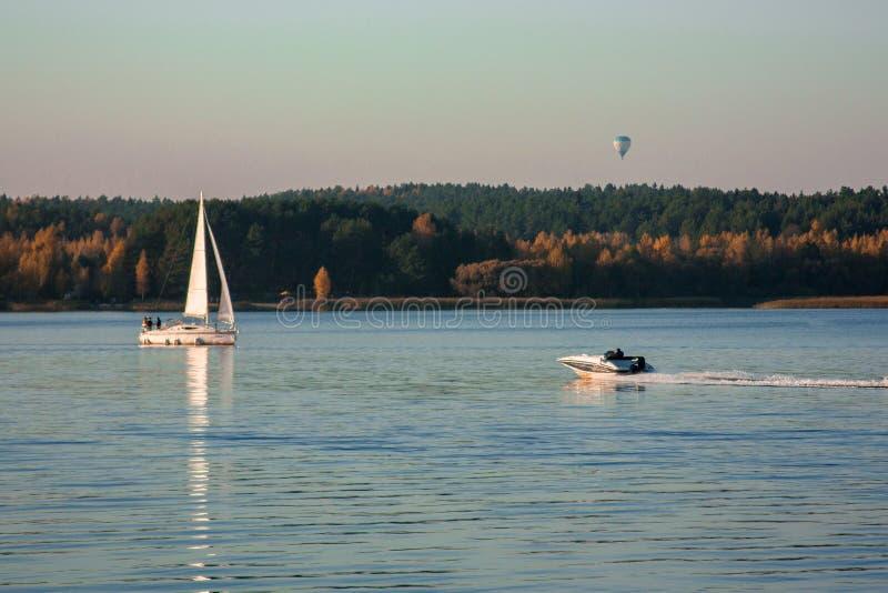 Paisaje hermoso, yate, globo, pájaros y puesta del sol del lago Línea azul de las ondas, del barco y del horizonte en el agua imágenes de archivo libres de regalías