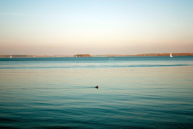 Paisaje hermoso, yate, pájaros y puesta del sol del lago Línea azul de las ondas, del barco y del horizonte en el agua Fondo herm fotos de archivo libres de regalías
