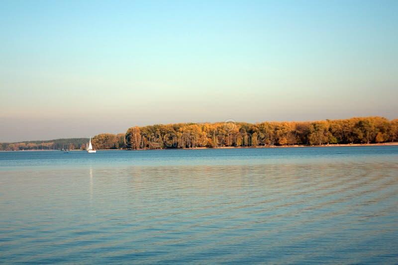 Paisaje hermoso, yate, y puesta del sol del lago Línea azul de las ondas, del barco y del horizonte en el agua Fondo hermoso foto de archivo