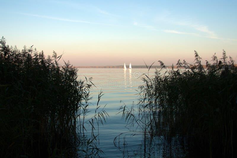 Paisaje hermoso, yate, y puesta del sol del lago Línea azul de las ondas, del barco y del horizonte en el agua Fondo hermoso imagen de archivo libre de regalías